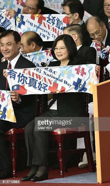 Taiwan President Tsai Ingwen hols up a sign that reads 'good to have you' during National Day celebrations in front of the Presidential Palace in...