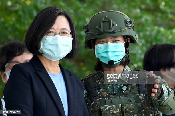 Taiwan President Tsai Ingwen listens to a masked soldier amid the COVID19 coronavirus pandemic during her visit to a military base in Tainan southern...