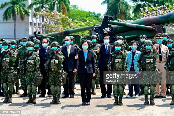 Taiwan President Tsai Ingwen seen wearing a face mask amid the COVID19 coronavirus pandemic alongside soldiers and officials poses for a photograph...