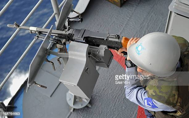 A Taiwan sailor operates a machine gun on a Kiddclass destroyer as it patrols in the Taiwan strait during a drill on May 15 2013 aimed at defending...