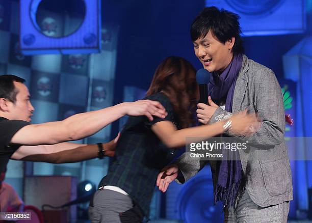 Taiwan singer Jeff Chang reacts as a fan tries to embrace him during a fan club activity to promote his new album on October 11 2006 in Nanjing of...