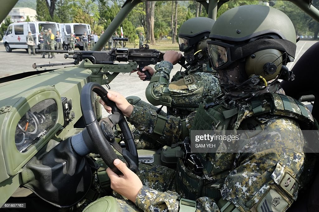 Taiwan special forces personnel pose for photos on a vehicle