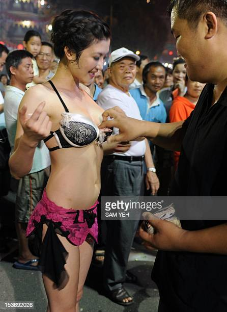 TaiwanculturereligionFEATURE by Amber Wang In a picture taken on August 31 a dancer receives a tip during a temple festival in northern Taoyuan...