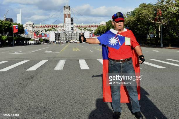A Taiwanese activist is draped with the Taiwan national flag outside the main entrance of the National Day ceremony in Taipei on October 10 2017...