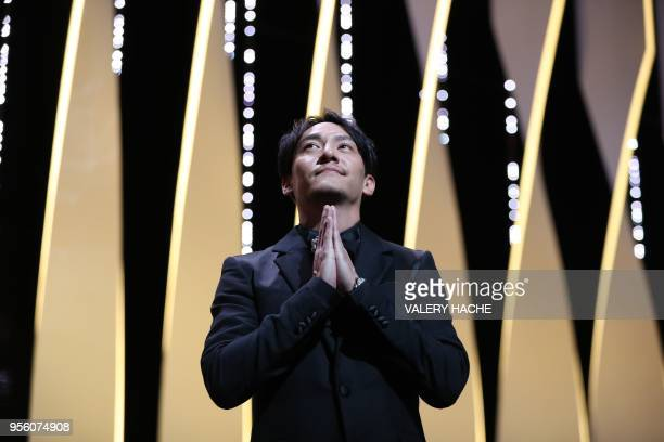 Taiwanese actor and member of the Feature Film Jury Chang Chen gestures as he arrives on stage on May 8 2018 for the opening ceremony of the 71st...