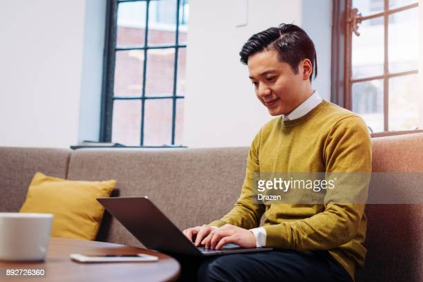 Taiwanese businessman working on laptop in modern office