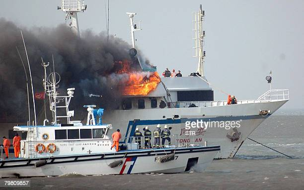 Taiwanese coastguards closely monitor China's ferryboat 'Tong An' which was engulfed by a fire outside Kinmen a Taiwancontrolled fortified island off...