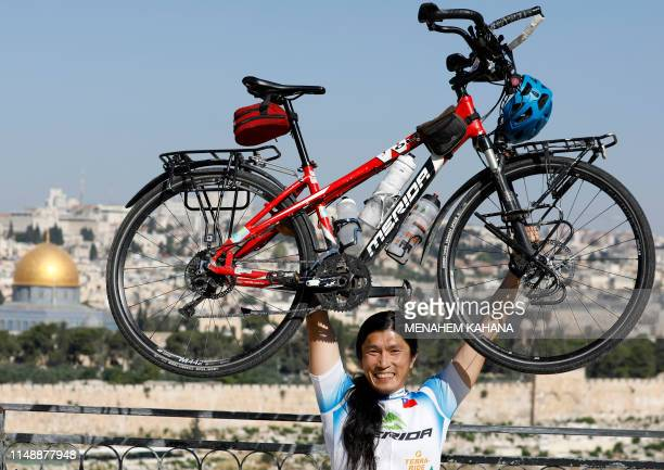 Taiwanese cycler and world traveller Jacky Chen poses while lifting his bicycle on the Mount of Olives overlooking the Old City of Jerusalem and the...