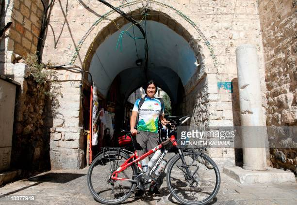 Taiwanese cycler and world traveller Jacky Chen poses with his bicycle in the Old City of Jerusalem on June 10 2019 It was four years ago when Jacky...