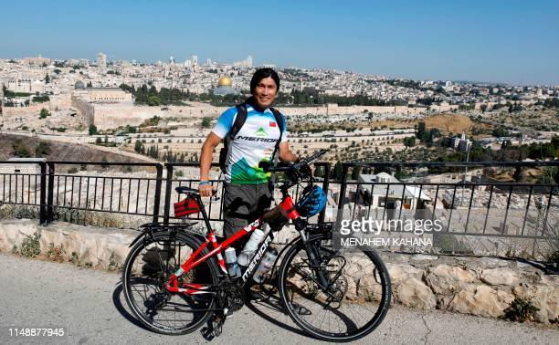 Taiwanese cycler and world traveller Jacky Chen poses with his bicycle on the Mount of Olives overlooking the Old City of Jerusalem and the Dome of...