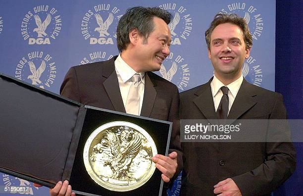 Taiwanese director Ang Lee is joined by British director Sam Mendes as he poses with his award for outstanding directorial achievement in a feature...