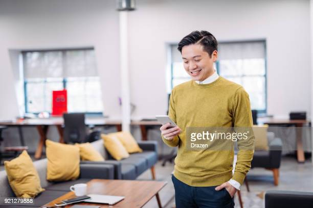 Taiwanese man using smart phone to send text message
