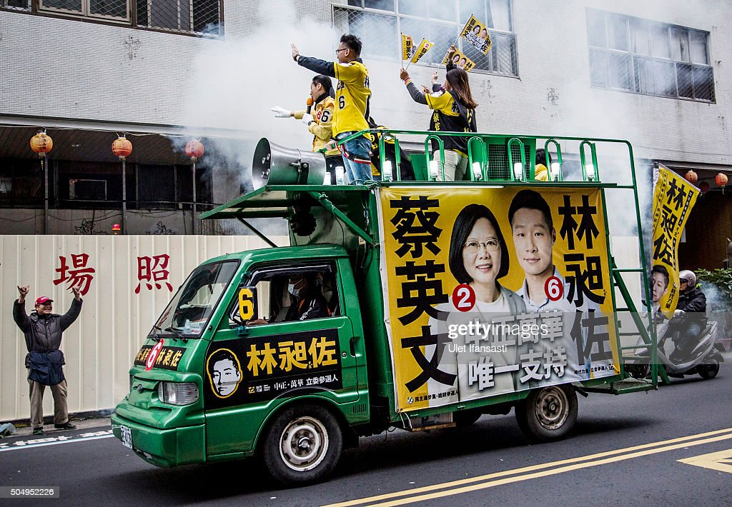 A Taiwanese man waves to campaign supporters of Democratic Progressive Party (DPP) presidential candidate Tsai Ing-wen, ahead of the Taiwanese presidential election on January 14, 2016 in Taipei, Taiwan. Voters in Taiwan are set to elect Tsai Ing-wen, the chairwoman of the opposition Democratic Progressive Party, to become the island's first female leader.