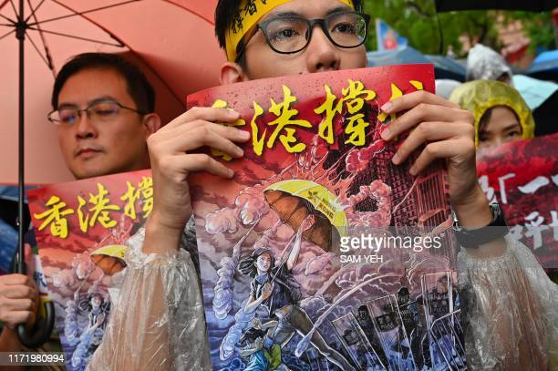 TOPSHOT Taiwanese march in the streets outside the parliament in Taipei during a demonstration to support Hong Kong's prodemocracy protests on...