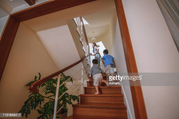 taiwanese mother and young sons ascending staircase - geographical locations stock pictures, royalty-free photos & images