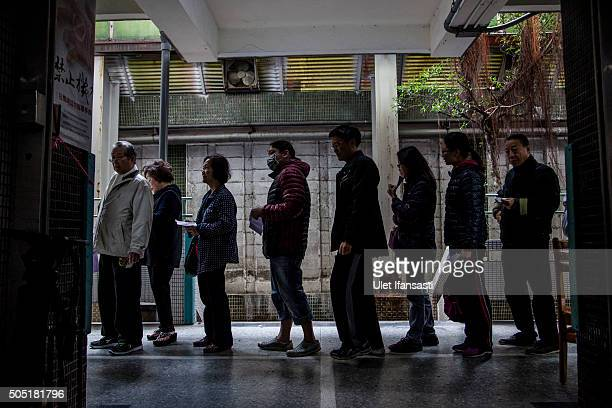 Taiwanese people stand in line to vote at a polling station on January 16 2016 in Taipei Taiwan Voters in Taiwan are set to elect Tsai Ingwen the...