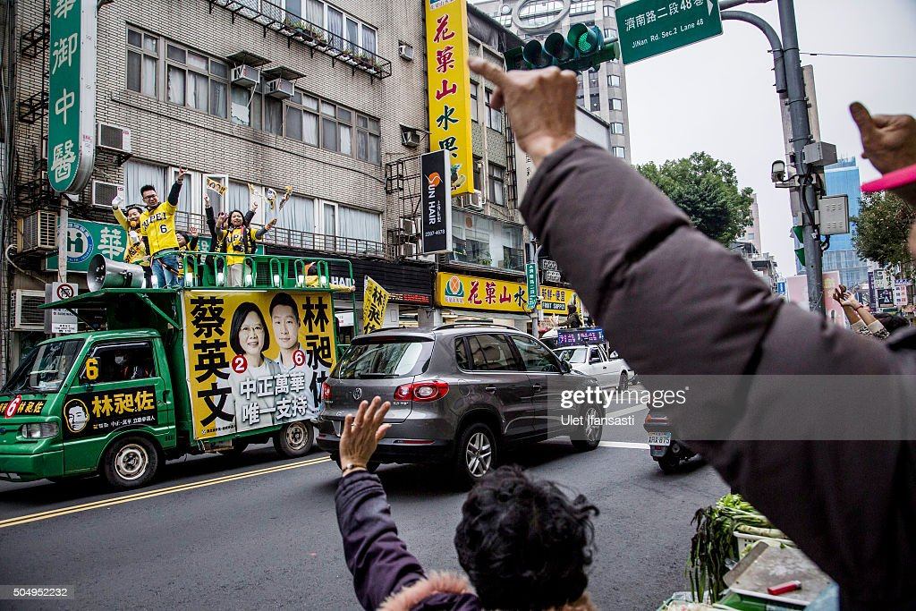 Taiwanese people wave to campaign supporters of Democratic Progressive Party (DPP) presidential candidate Tsai Ing-wen, ahead of the Taiwanese presidential election on January 14, 2016 in Taipei, Taiwan. Voters in Taiwan are set to elect Tsai Ing-wen, the chairwoman of the opposition Democratic Progressive Party, to become the island's first female leader.