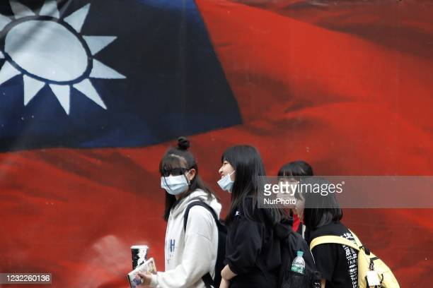 Taiwanese people wearing a face walk mask pass a Taiwan flag banner, amid heated tensions with Beijing, in Taipei, Taiwan, 11 April 2021. With more...