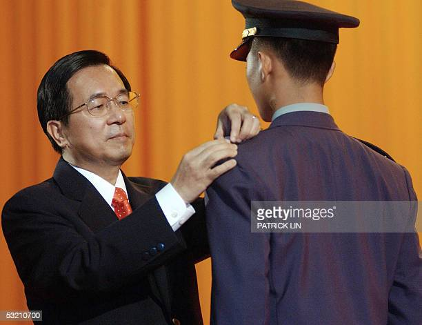 Taiwanese President Chen Shuibian confers military rank to a cadet during the joint graduation ceremony for the defense university the army the air...