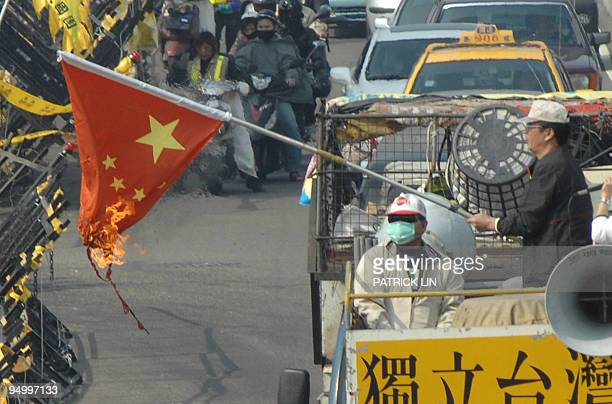 A Taiwanese protester carries a burning Chinese flag during a parade outside a hotel in Taiwan's central Taichung city on December 22 2009 to...