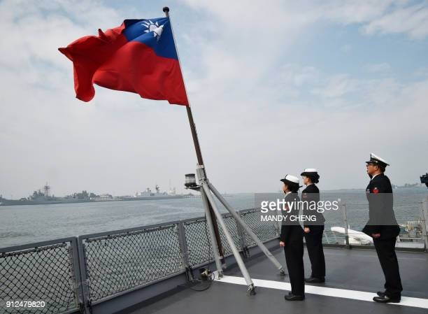 Taiwanese sailors salute the island's flag on the deck of the Panshih supply ship after taking part in annual drills, at the Tsoying naval base in...