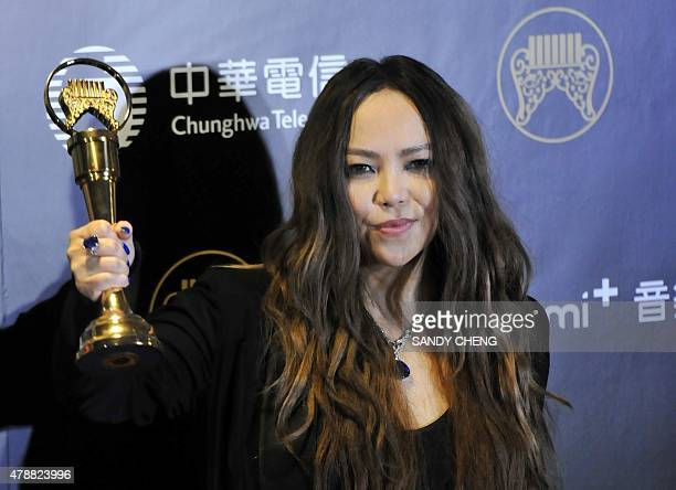 Taiwanese singer aMEI poses with her trophies after winning the Best Female Mandarin Singer award at the 26th Golden Melody Awards in Taipei on June...