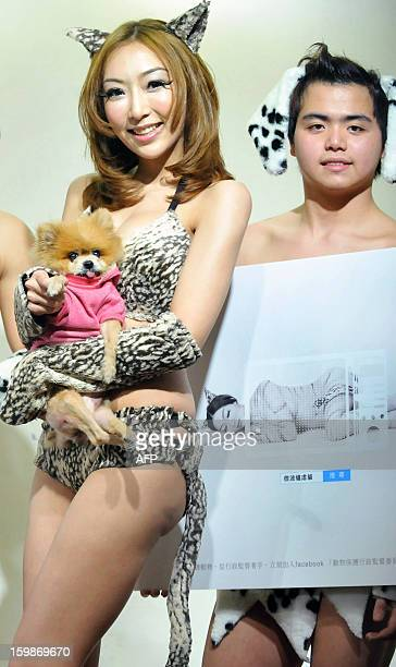 Taiwanese singer Mina Lee holds a dog while a male model carries an animal rights poster during a press conference in Taipei on January 22 2013 The...