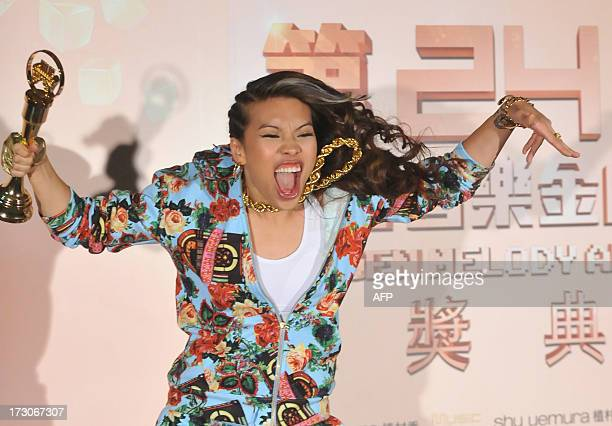 Taiwanese singer Miss Ko jumps and displays a trophy for photographers after winning the Best New Artist at the 24th Golden Melody Awards in Taipei...