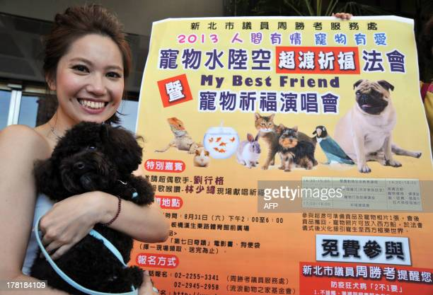 Taiwanese singer Singger Liu poses with a dog during a press conference in New Taipei City on August 27, 2013. A prayer service and concert will be...