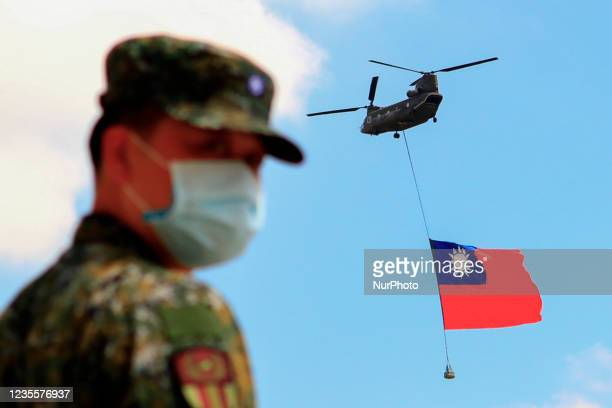 Taiwanese soldiers stand guard as a Chinook Helicopter carrying a tremendous Taiwan flag flies over a military camp, as part of a rehearsal for the...