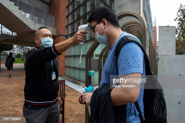 Taiwanese students get their temperature checked as they enter the Taipei American school on March 18, 2020 in Taipei, Taiwan. Taiwan, Singapore and...