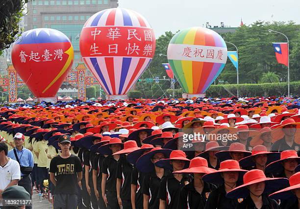 Taiwanese students wearing colourful costumes and hats parade during celebrations to mark National Day in Taipei on October 10 2013 Taiwan President...