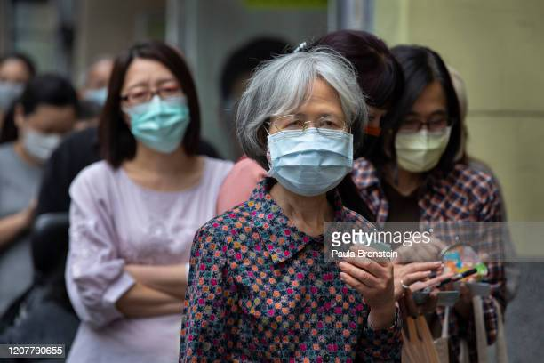 Taiwanese wait in line at a pharmacy to pick up masks pre ordered online on March 18 2020 in Taipei Taiwan Taiwan Singapore and Hong Kong have had...