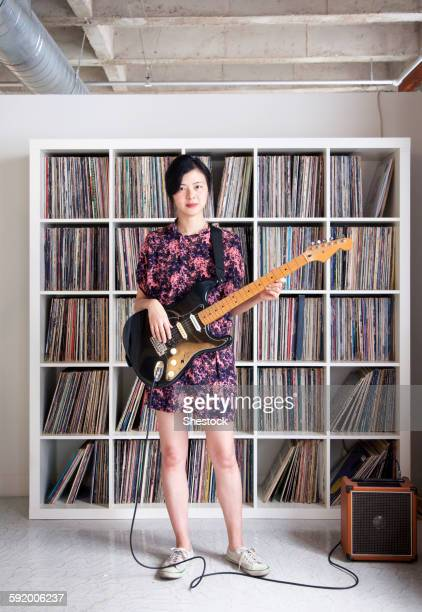 Taiwanese woman playing electric guitar near record collection