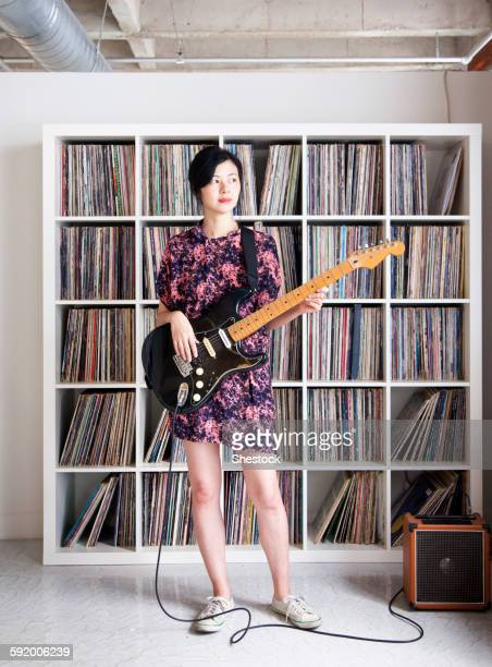 taiwanese woman playing electric guitar near record collection - エレキギター ストックフォトと画像