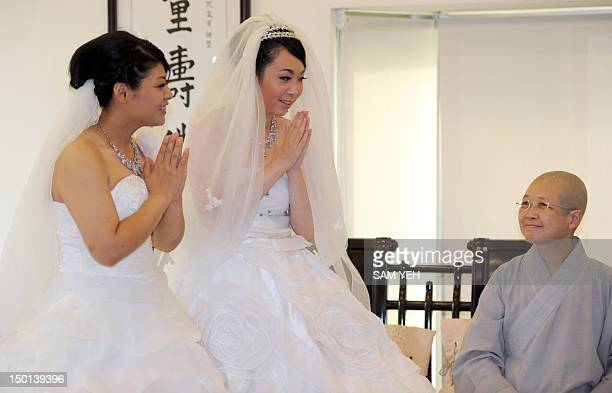 Taiwanese women Fish Huang and her partner You Yating accept the blessing from Master Shih Chaohui during their samesex Buddhist wedding ceremony in...