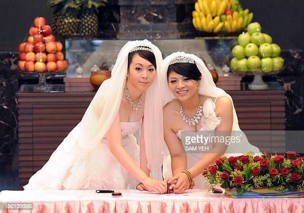 Taiwanese women Fish Huang and her partner You Yating cast their stamps during their samesex Buddhist wedding ceremony in Taoyuan on August 11 2012...