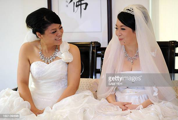Taiwanese women Fish Huang and her partner You Yating smile during their samesex Buddhist wedding ceremony in Taoyuan on August 11 2012 The two women...