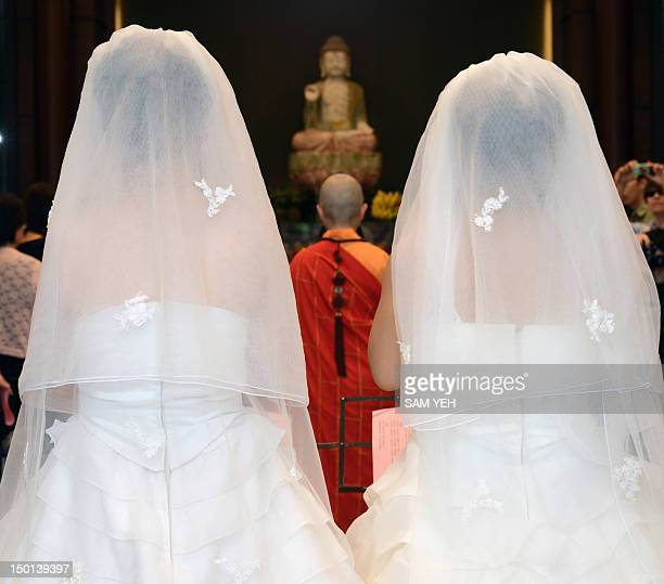 Taiwanese women Fish Huang and her partner You Yating stand together during their samesex Buddhist wedding ceremony in Taoyuan on August 11 2012 The...