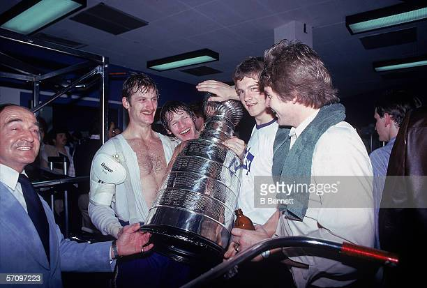 Taiwanese-born American professional hockey player Rod Langway , defenseman for the Montreal Canadiens, stands with his teammates and celebrates with...