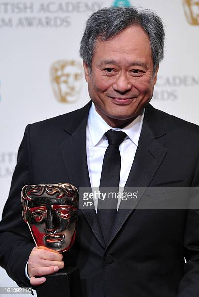 Taiwaneseborn US film director Ang Lee poses with the Cinematography award for Claudio Miranda for his work on the film Life of Pi during the annual...