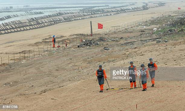 TaiwanpoliticsChinaMaanniversary by Benjamin Yeh A team of Taiwan army soldiers wearing protective gear work to clear landmines near the seashore of...