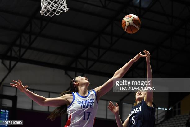 Taiwan's Bao Hsile battles for the ball against Unified Korea's Park Hyejin in the women's basketball preliminary group A match between Taiwan and...