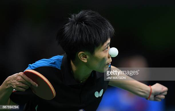 Taiwan's Cheng IChing eyes the ball as she serves against China's Li Xiaoxia in their women's singles quarterfinal table tennis match at the...
