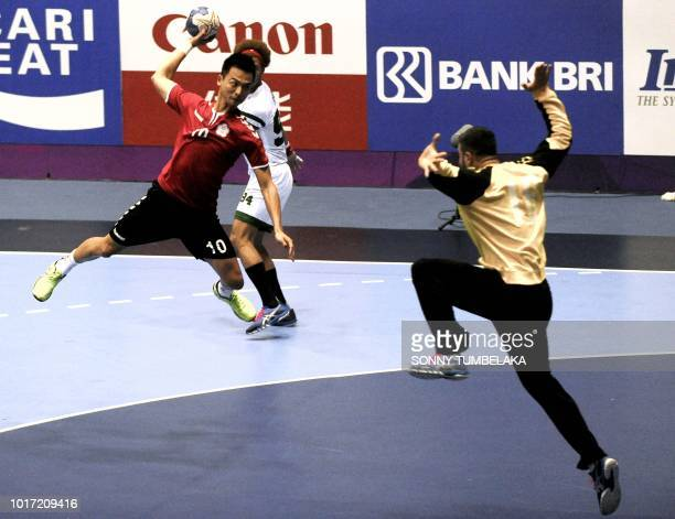 Taiwan's Chiu Yifan throws the ball as Iraq's Allazawi Ahmed Makki Sal tries to stop him during the men's handball preliminary Group D match between...