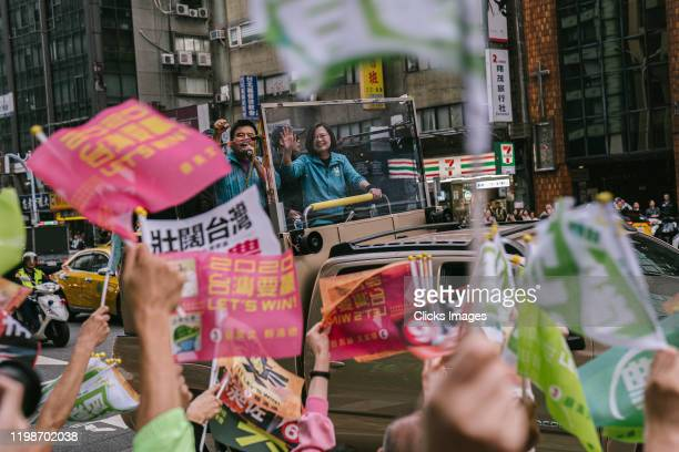 Taiwan's current president and Democratic Progressive Party presidential candidate, Tsai Ing-wen, waves to supporters from a car roof during a...