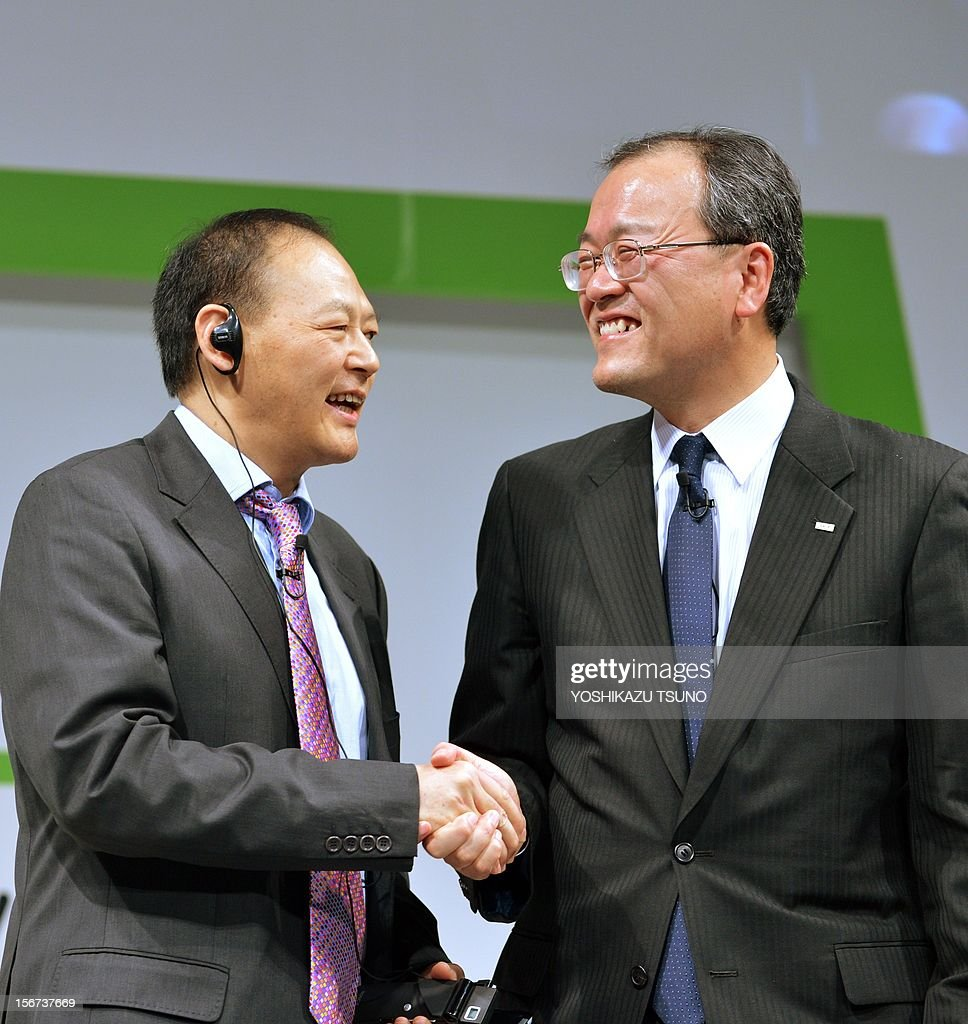 Taiwan's electronics giant HTC CEO Peter Chou (L) shakeds hands with KDDI president Takashi Tanaka as they introduced the new smartphone 'HTCJ butterfly' for Japanese mobile carrier KDDI in Tokyo on November 20, 2012. The new smartphone has a quad-core CPU, 5-inch sized high-definition LCD display and an 8 mega-pixel CMOS camera on its slim body. AFP PHOTO / Yoshikazu TSUNO