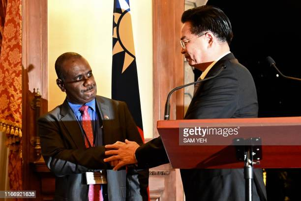 Taiwan's Foreign Minister Joseph Wu shakes hands with Solomon Islands' Foreign Minister Jeremiah Manele during a press conference at the Taipei Guest...