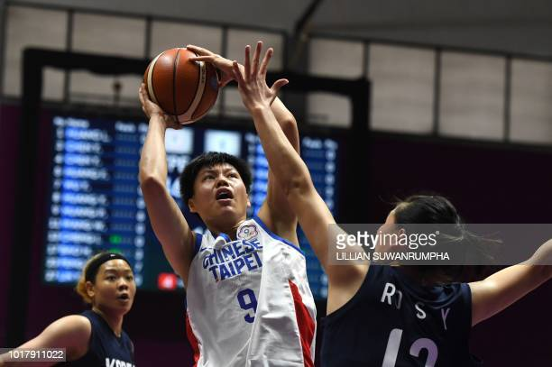 Taiwan's Huang Pingjen goes for the basket against Unified Korea's Ro Suk Ying in the women's basketball preliminary group A match between Taiwan and...