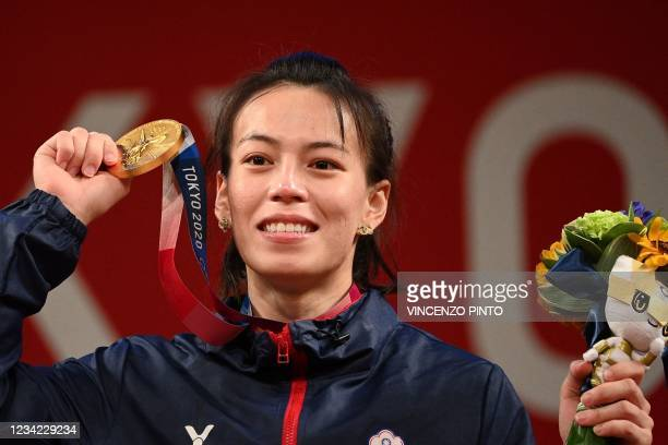 Taiwan's Kuo Hsing-chun shows her gold medal after the victory ceremony of the women's 59kg weightlifting competition during the Tokyo 2020 Olympic...
